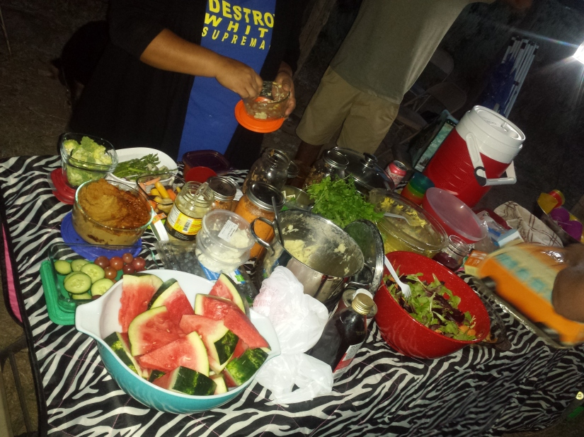 A potluck spread featuring cultural foods and community member with a shirt that reads Destroy white supremacy