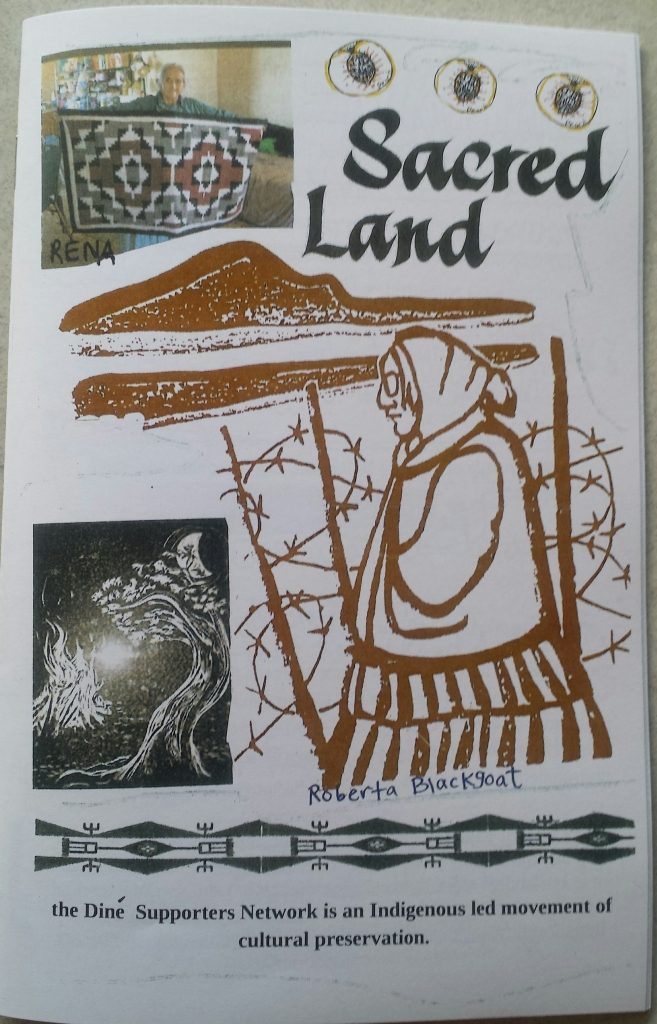 Zine cover of Sacred Land. thick brown-red outline drawing of Roberta Blackgoat is center right aftont a bobwire fence and Big Mountain. Rena Babbit Lane arms wide displays her hand woven rug.