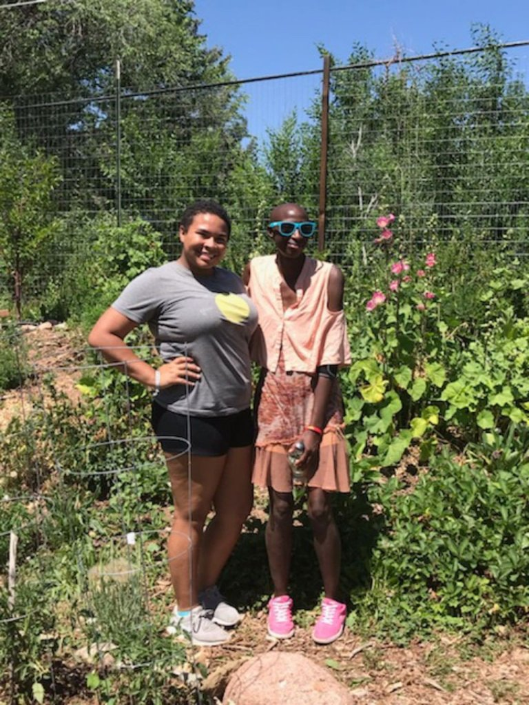 Two beings pose in the garden after volunteering