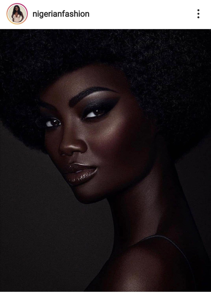 Dark skinned being with tight afro and thin strapped top