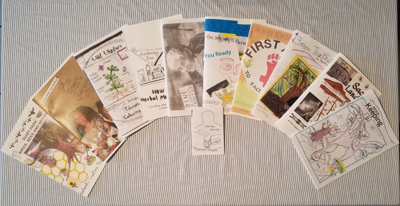 Spread of our 11 zines on a blue striped cloth