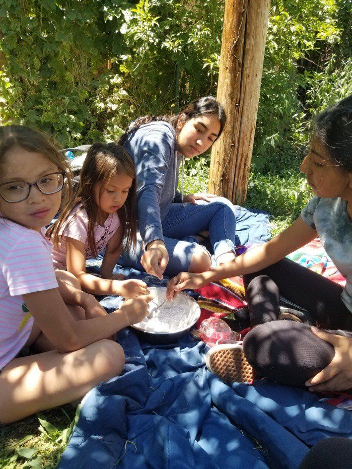 Four Indigenous youth making foot powder on a blue blanket under the Trees