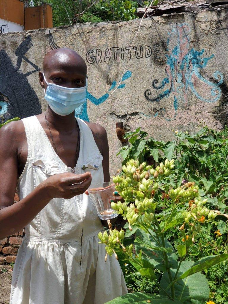 kuwa jasiri (the one/ellx) in the Huerto Feliz garden collecting Tobacco Seeds
