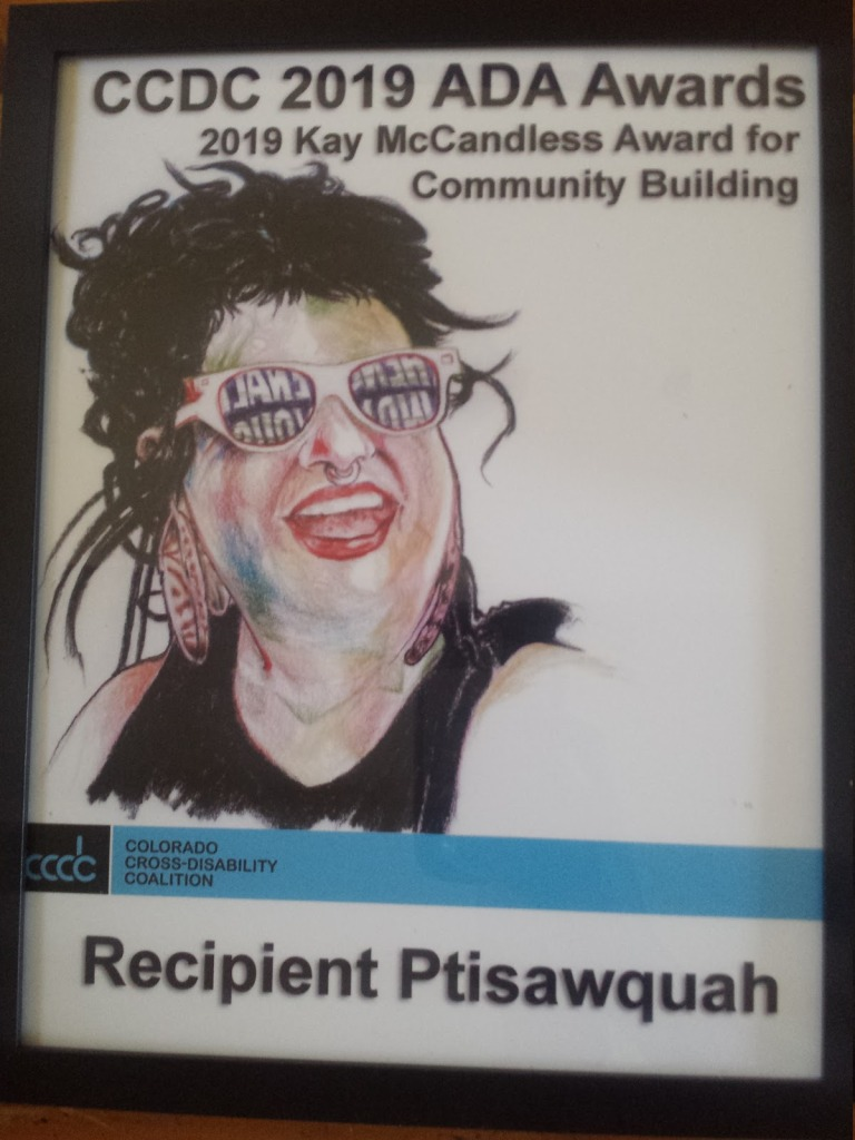 Drawing of ptisawquah (they/them) on a plaque receiving a Community Building Award from the Disability Coalition
