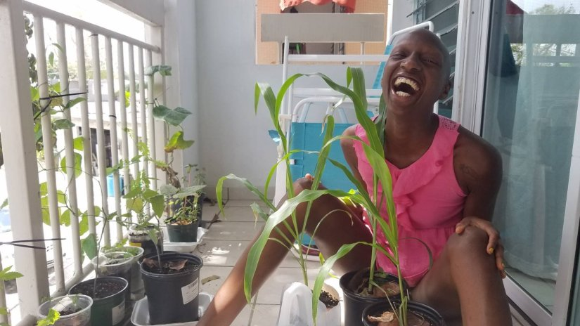 kuwa jasiri (the one) laughs while on the porch interacting with the container garden